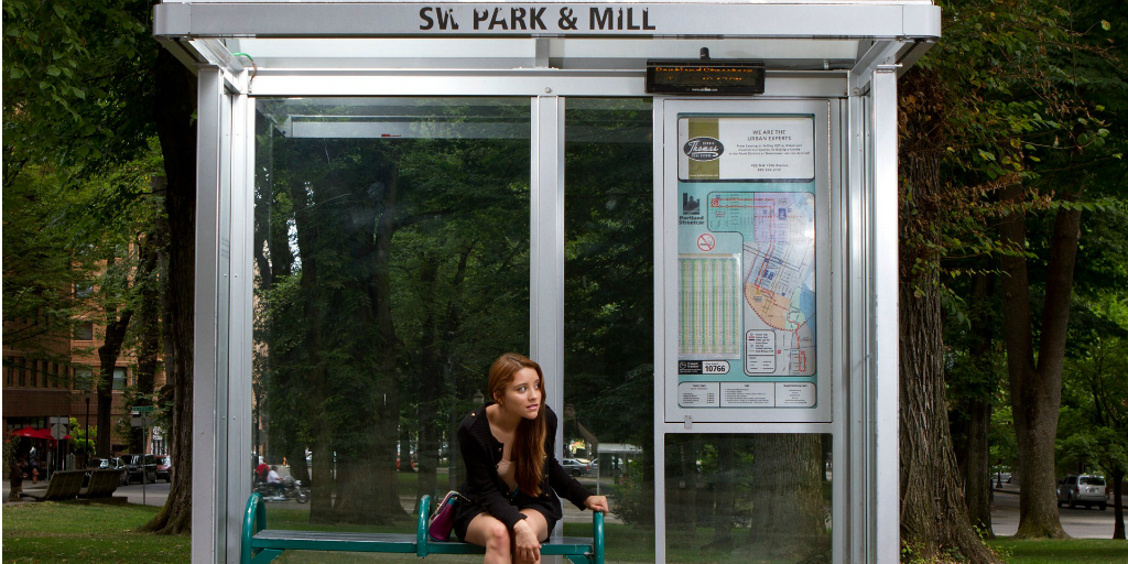 A woman waiting for a bus under a bus shelter.