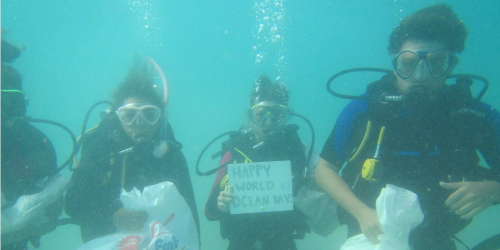Participants of the Fiji Caqalai program celebrate World Oceans Day with a dive against ocean plastic pollution