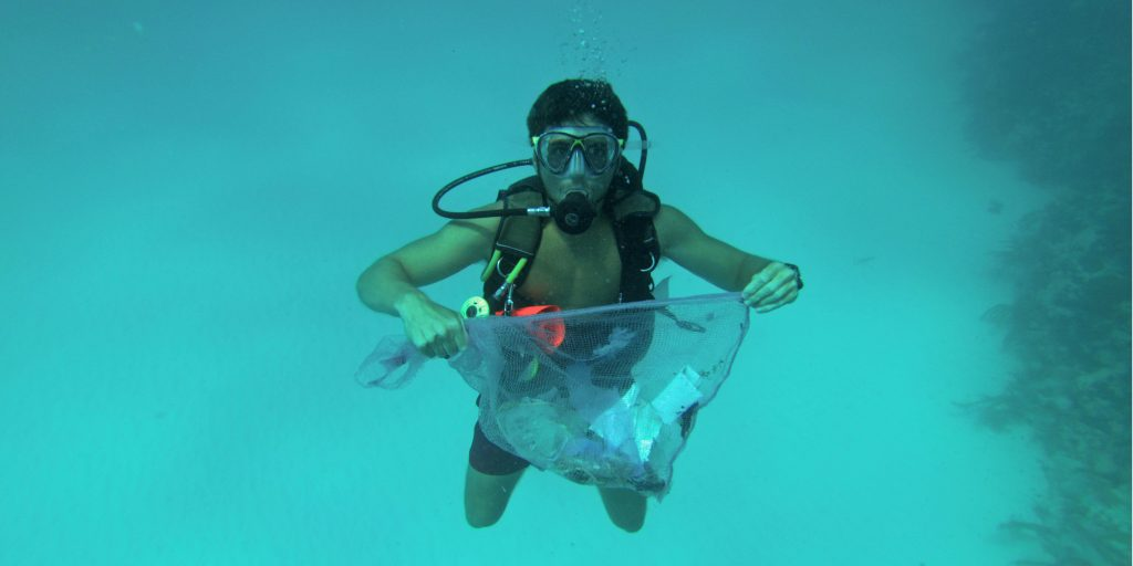 Plastic pollution endangers marine life. Here, a GVI volunteer helps clean up the ocean floor during a dive against debris, in Mexico.