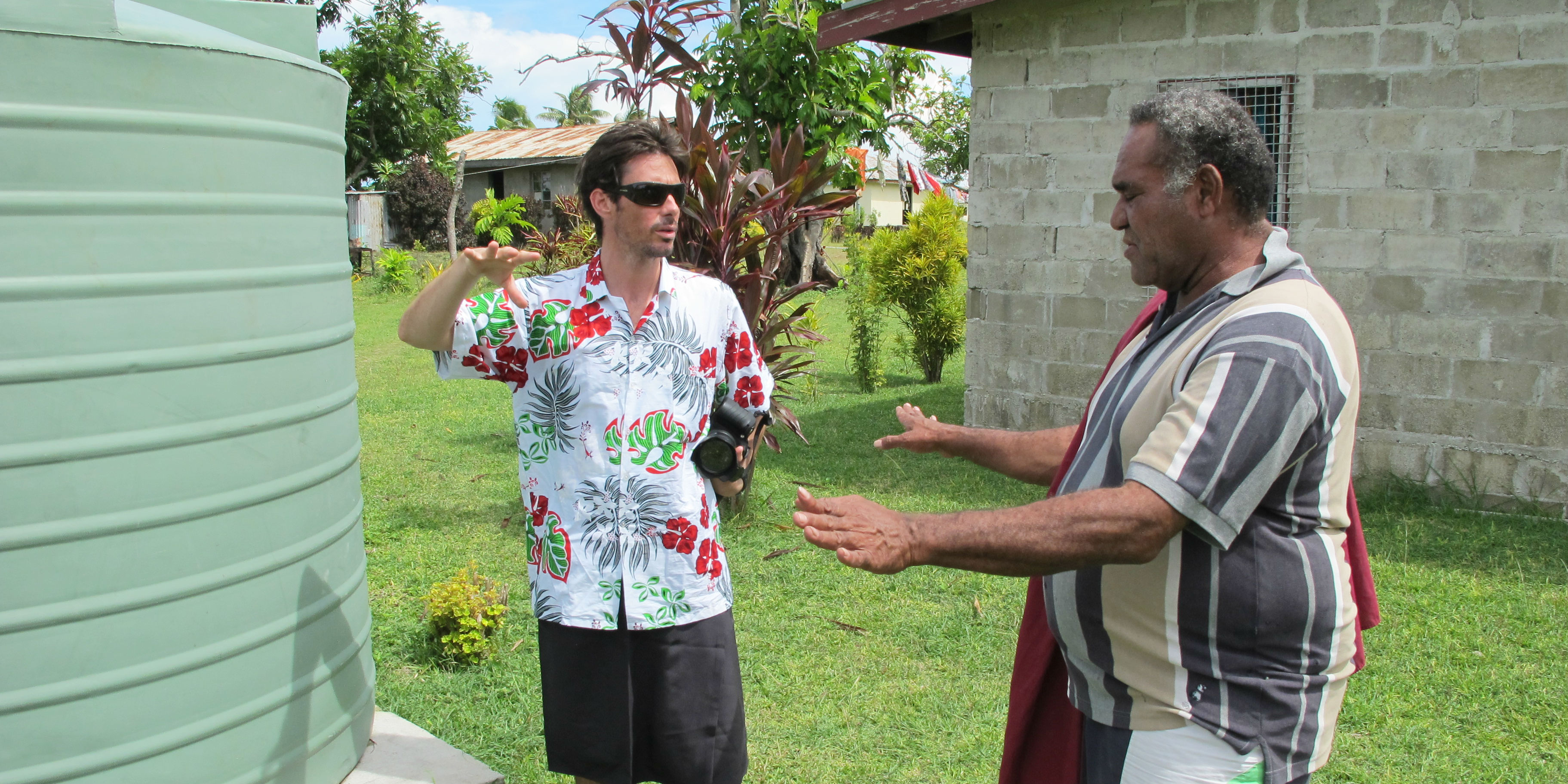 A GVI participant engages with a community member about a water tank, in Fiji. Working on water security is one of the best things you can do as an adult volunteer.