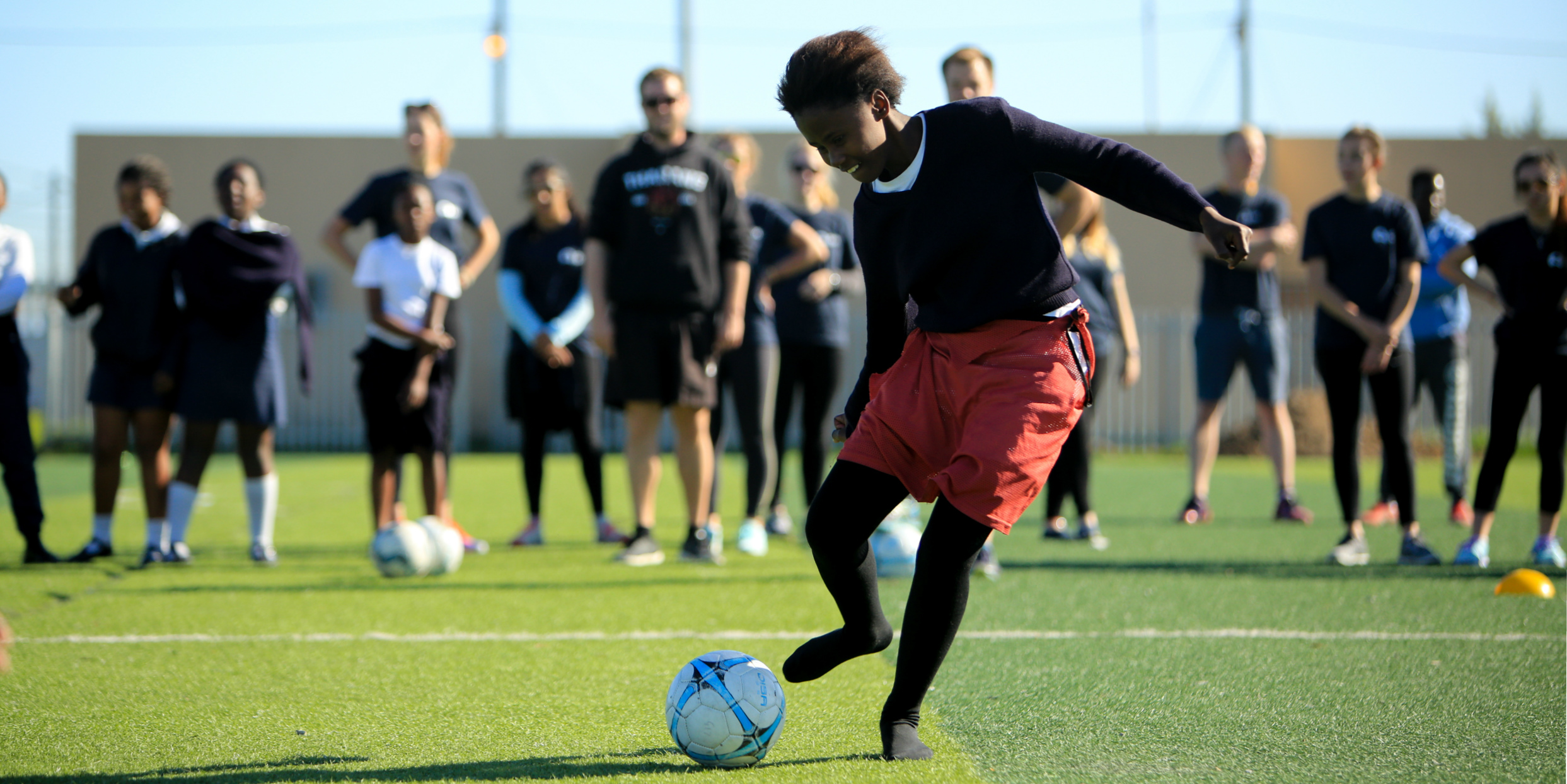 A girl goes in to kick a soccer ball triumphantly. As part of activities for women's empowerment, GVI participants facilitate sports lessons with Cape Town youth.
