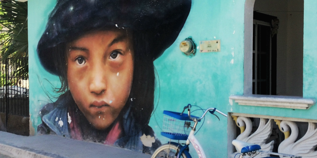 A mural of a Mexican girl on the wall of a home in Cancun with.