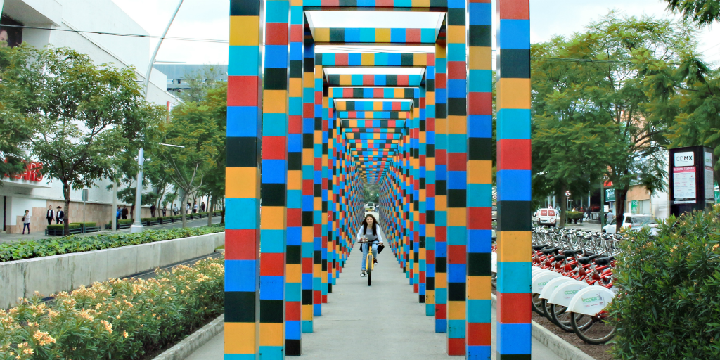 A girl riding her bike down a pathway under an art deco archway in Peurto Morelos, Mexico.