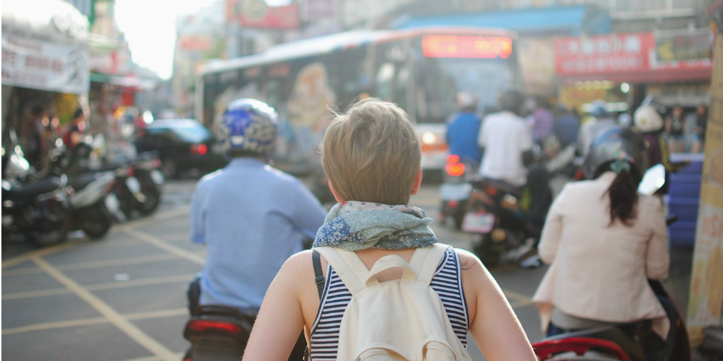 A woman wearing a back pack, walking into a crowded street.