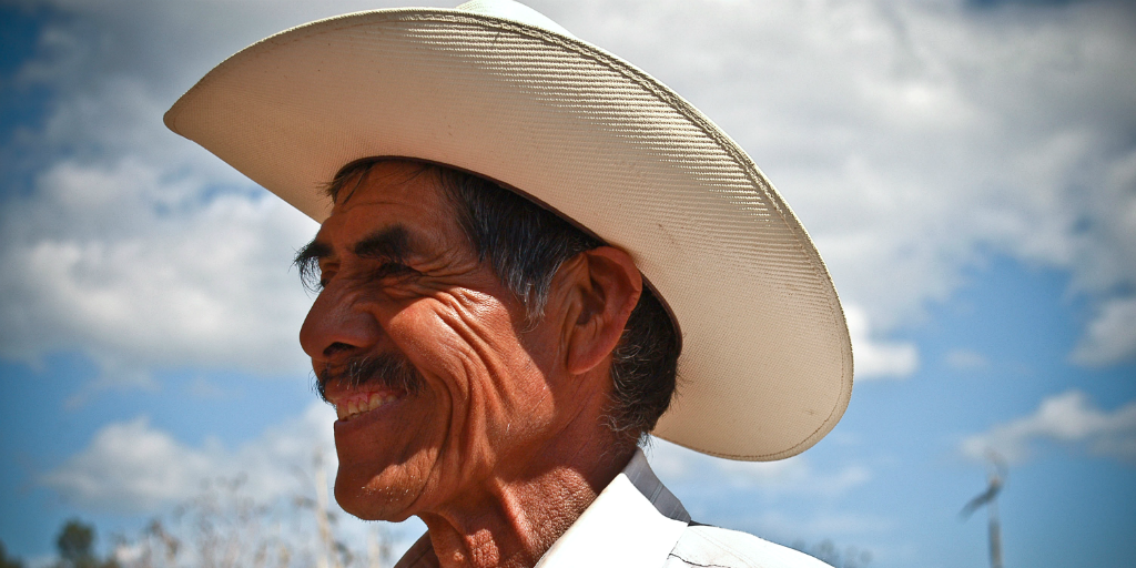 A Mexican man in a cowboy hat smiling, and looking into the distance.