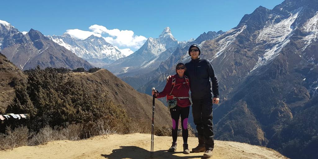 Two hikers pose for a photo with a mountain peak in the background.