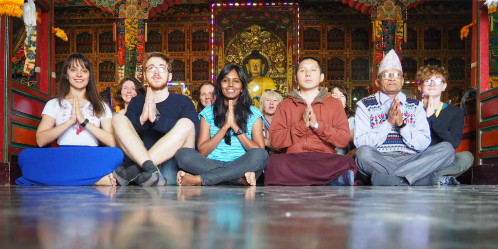 Volunteers sitting on the floor of a temple with a Nepalese man.