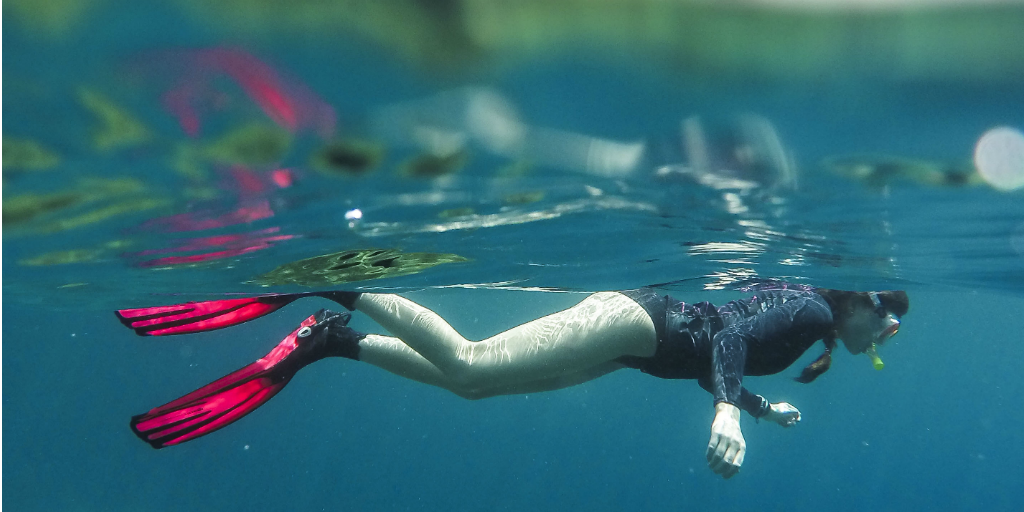 A diver swimming just beneath the surface of the water.