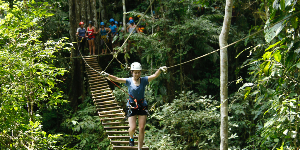 A volunteer wearing a harness, walking across a rope bridge.